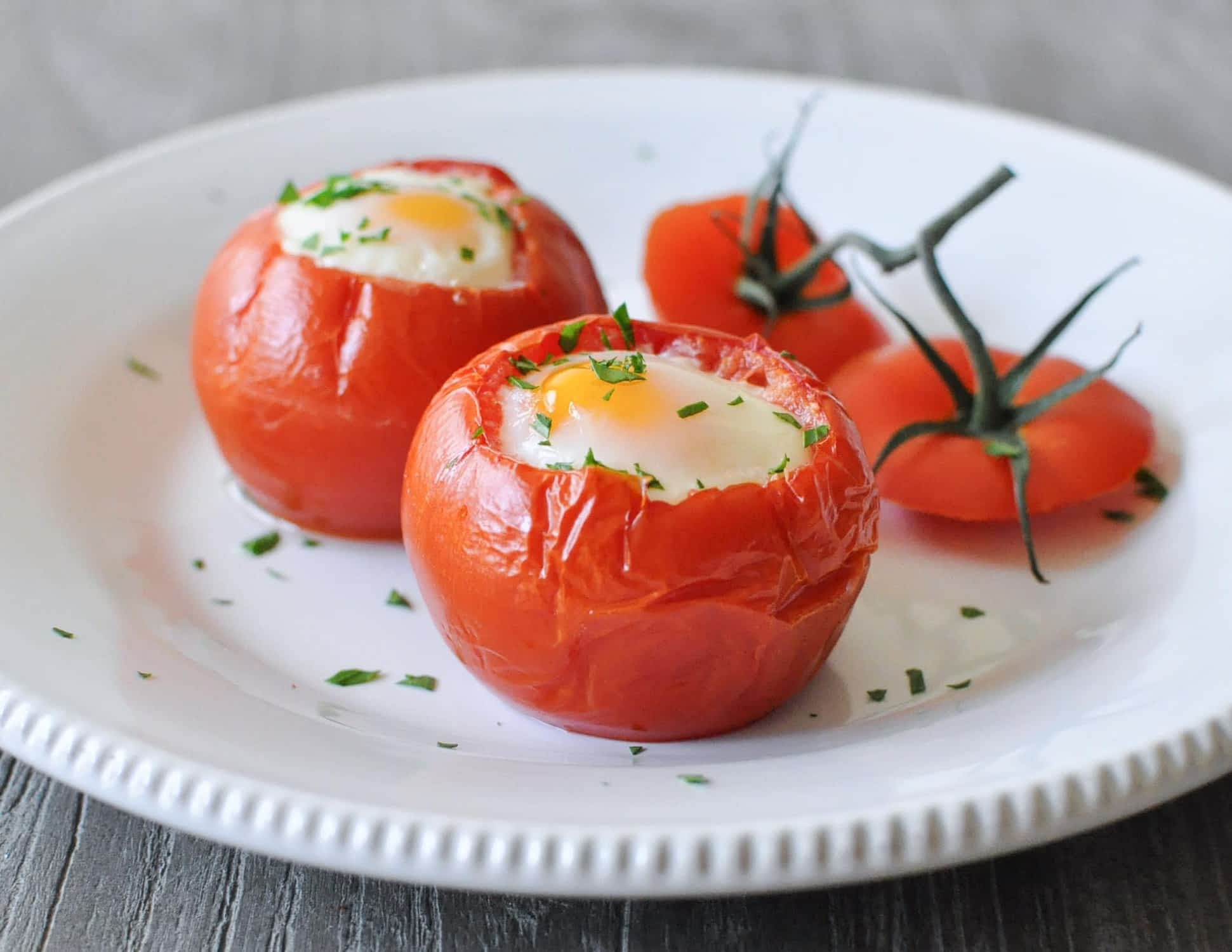 a white plate of two baked tomato eggs