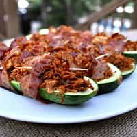 bacon wrapped stuffed zucchinis on a white plate on top of a burlap covered table