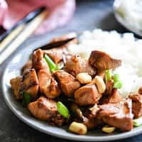 paleo kung pao chicken with rice on a gray plate on a dark gray surface