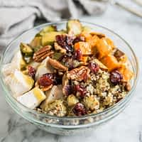 quinoa bowls with sweet potatoes, chicken, brussels spouts, pecans, and cranberries in a glass bowl on a marble countertop