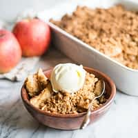 paleo apple crisp in a wooden bowl topped with a scoop of ice cream on a marble surface