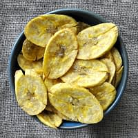 overhead view of a blue bowl full of crispy baked yellow plantain chips on a gray surface