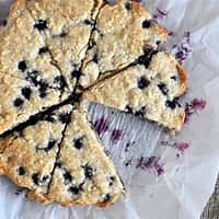 overhead view of blueberry scones on parchment paper cut into triangles