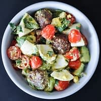overhead view of a white bowl filled with chopped hard boiled eggs, cherry tomatoes, avocados, cilantro and sausage meatballs on a dark gray surface