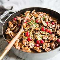 a casserole dish sitting on top of a white marble table with a wooden spoon dipped in filled with bacon cranberry cornbread stuffing with candied pecans, cranberries and chopped parsley on top