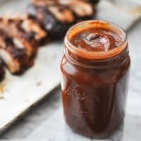 mason jar full of paleo barbecue sauce on a marble table with ribs blurred in the background