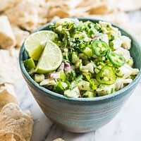 fish ceviche verde - fish ceviche topped with jalapenos and limes in a blue bowl on a marble slab surrounded by tortilla chips
