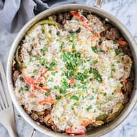 keto philly cheesesteak skillet - ground beef, peppers, and onions covered with provolone cheese and garnished with parsley on a marble board