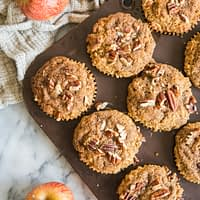 paleo apple cinnamon muffins in a muffin tin on a marble board with apples and a grey cloth surrounding them