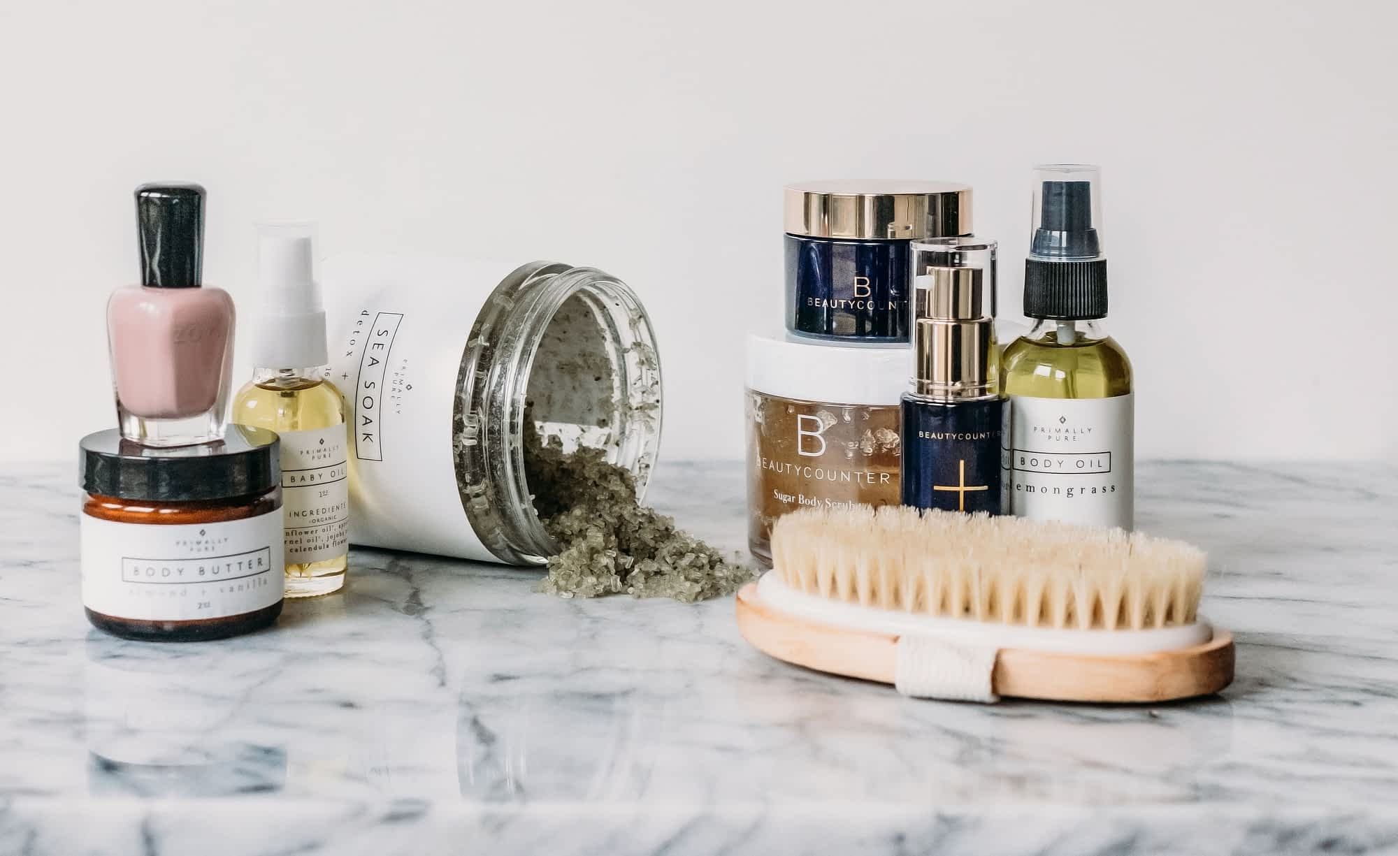 safer beauty items including nail polish, body butter, and body scrub on a marble surface