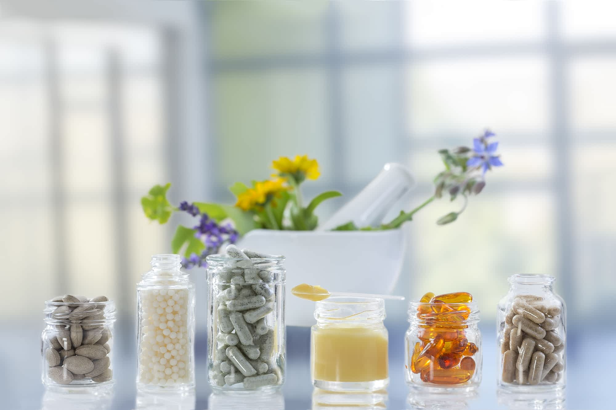 natural allergy remedies - supplements in glass jars lined up