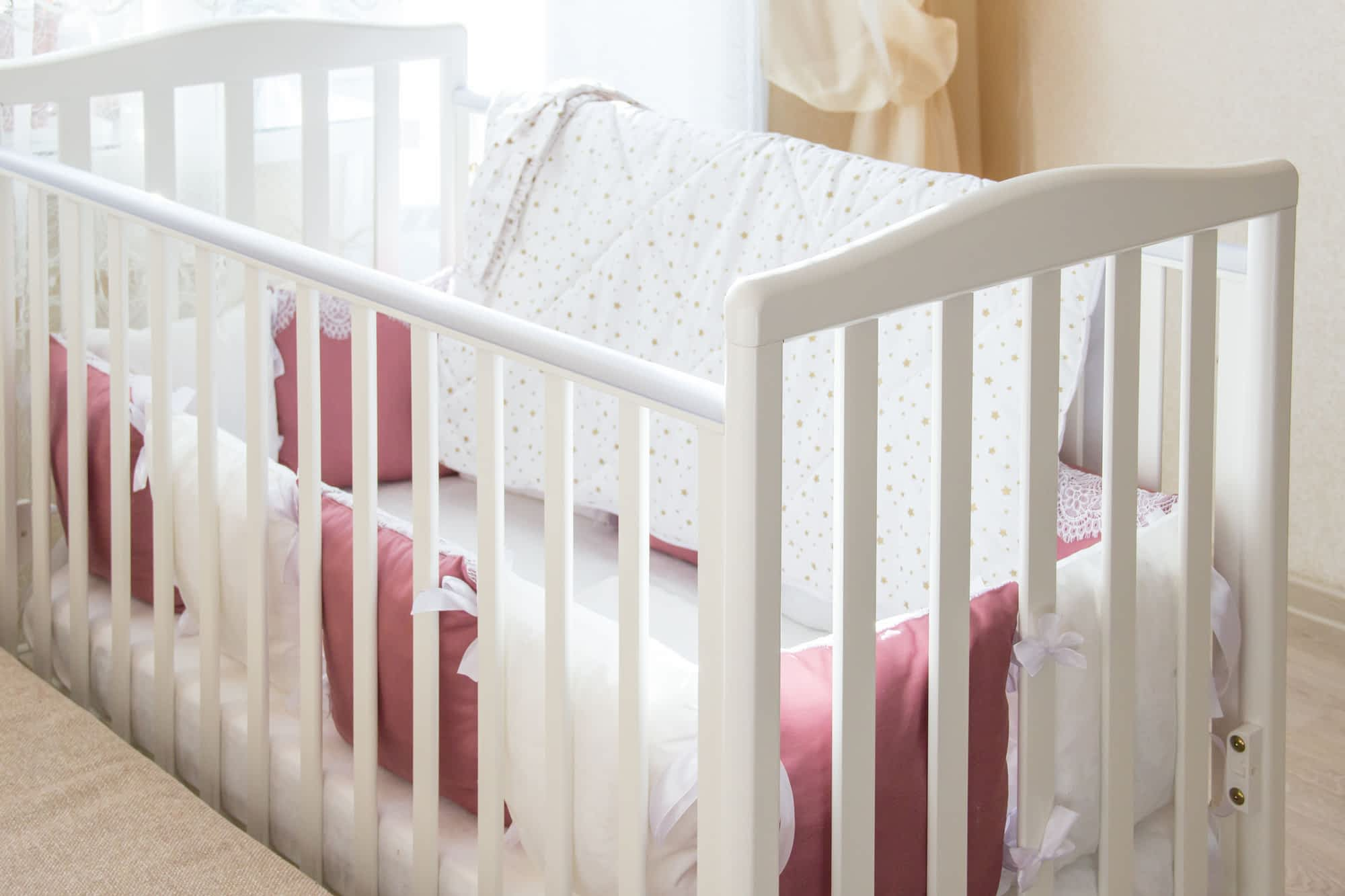white crib with pink pillows - sleep training methods