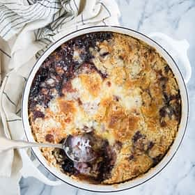 cherry dump cake in a round white baking dish with a scoop removed on a marble surface