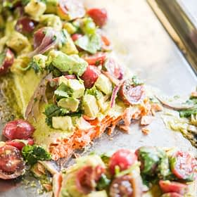 cilantro lime baked salmon topped with tomato avocado salsa on a sheet pan