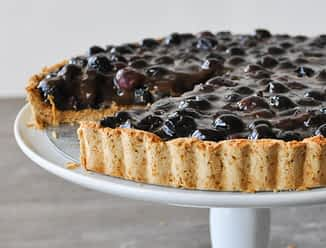 a blueberry tart on a white cake stand with one slice cut out