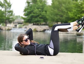 a woman in a fitness outfit in front of a river doing a situp