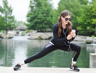 a woman with long dark pigtails lunges to the side in black activewear while wearing black sunglasses and looking down at her phone with her headphones in her ears with a green river in the background