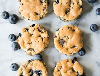 overhead view of blueberry sausage breakfast muffins on a white marbled table with fresh blueberries sprinkled around