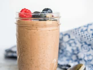 chocolate chia pudding in a mason jar topped with berries on a marble board with a spoon and blue towel