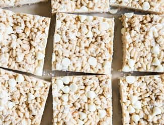 pumpkin spice rice krispie treats cut into squares on a sheet of parchment paper