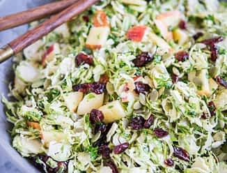 shaved brussels sprouts salad with apples, cranberries, and pumpkin seeds in a large gray bowl on a marble surface