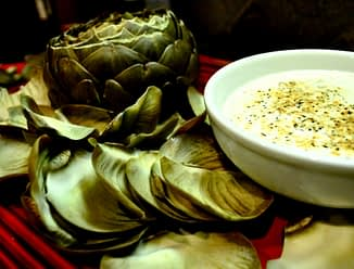 overhead view of cooked artichoke with a bowl of lemon artichoke dip