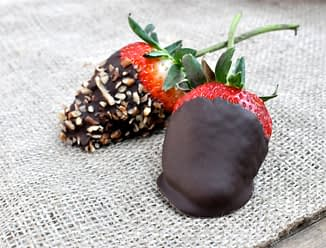 two chocolate covered strawberries one dipped in nuts