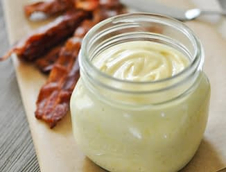 a glass jar of baconnaise on top of parchment paper with cooked bacon in the background