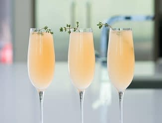 elderflower grapefruit mimosa in three champagne flutes