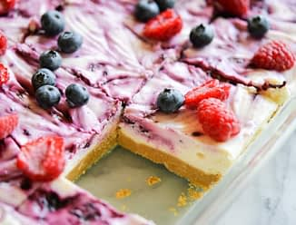 These no-bake berry cheesecake bars are a decadent dessert that are a serious crowd-pleaser! A simple gluten free graham cracker crust is topped with a luscious cheesecake filling, then swirled with a fresh berry sauce made with blueberries, raspberries, and blackberries. After a quick chill in the fridge, simply cut into squares and serve! The best part about these no-bake berry cheesecake bars is that they can be easily modified to be dairy free and paleo!