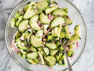 greek cucumber salad with fresh dill, red onions, feta, and a red wine vinegar dressing in a glass bowl on a marble countertop