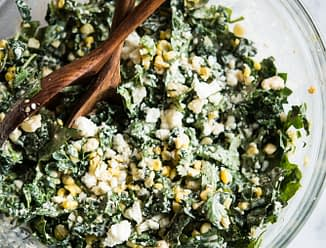 kale slaw in a bowl with corn and crumbled cotija cheese in a glass bowl with wooden serving spoons on a marble board