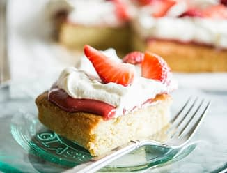 Strawberry shortcake - a square of vanilla cake is topped with strawberry sauce, whipped cream, and fresh strawberries and sits on a clear glass plate with a fork on a marble countertop.