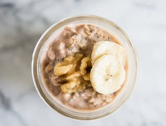 banana nut overnight oats in a mason jar topped with banana slices and walnuts
