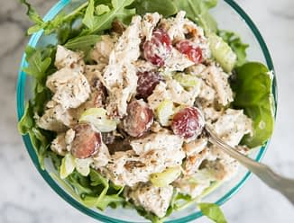 chicken salad with grapes and pecans over mixed greens in a glass bowl on a marble board