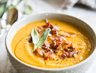 Instant pot pumpkin soup in a grey bowl topped with bacon and sage on a marble board