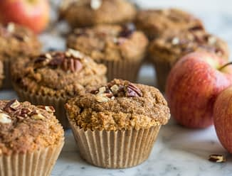 paleo apple cinnaomon muffins on a marble board surrounded by apples