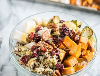 quinoa bowls with sweet potatoes, chicken, brussels spouts, pecans, and cranberries in a glass bowl on a marble countertop in front of a sheet pan with cubed chicken and sweet potatoes