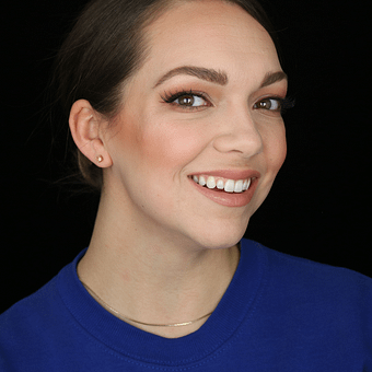 a woman with dark hair pulled pack in a purple shirt smiling at the camera