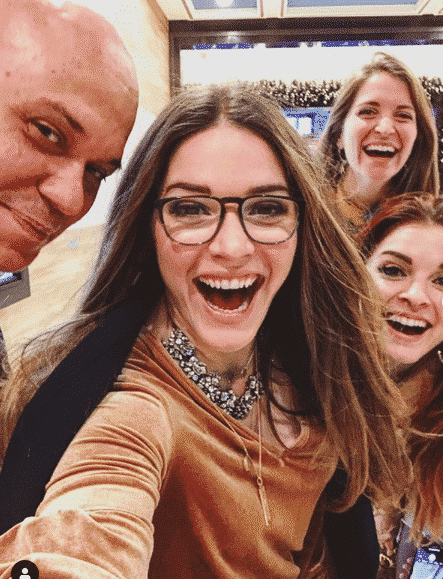 """a """"selfie"""" with three long haired smiling women and a bald man"""