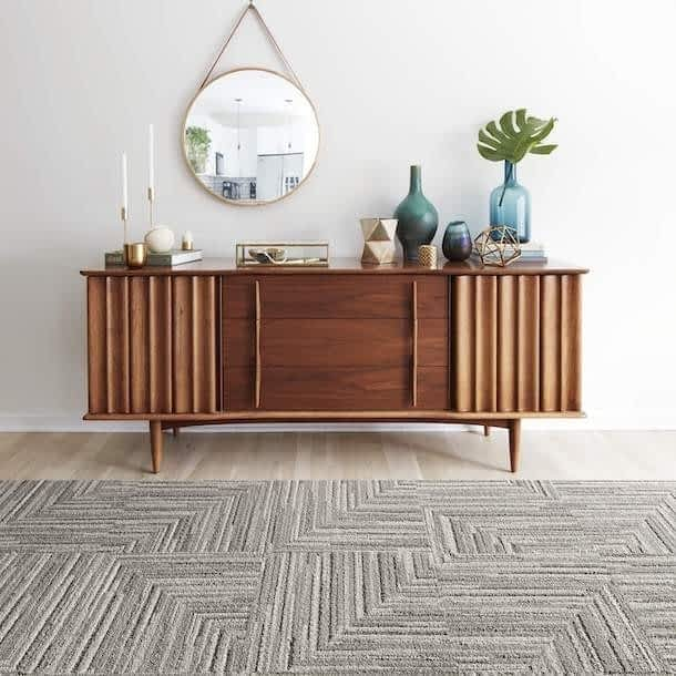 patterned grey and white rug in front of a wooden hutch