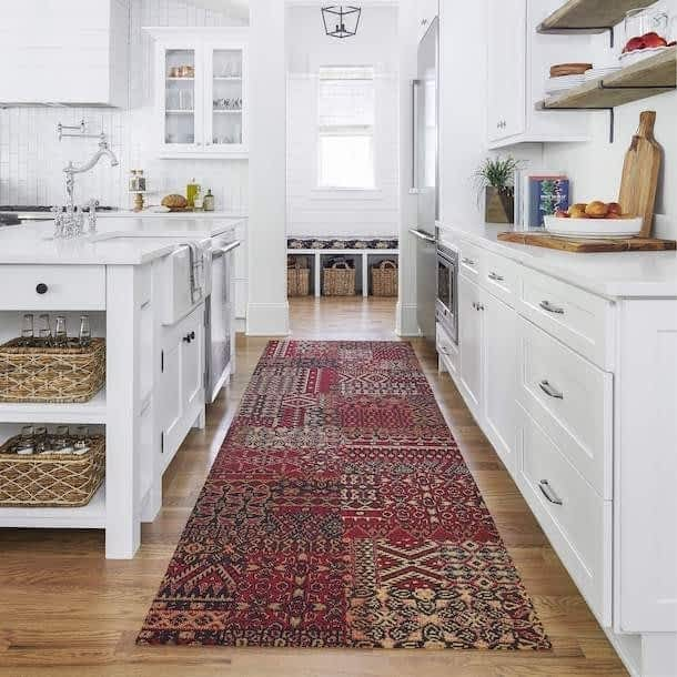 maroon patterned non-toxic rug on a wood floor in a white kitchen