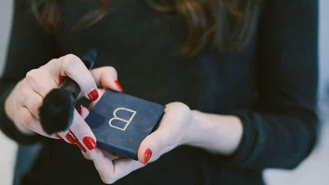 a woman in a black shirt with long dark hair and red fingernails holding a blush palette and a blush brush