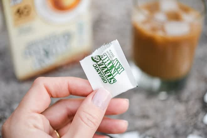 a hand holding one opened stevia in the raw packet