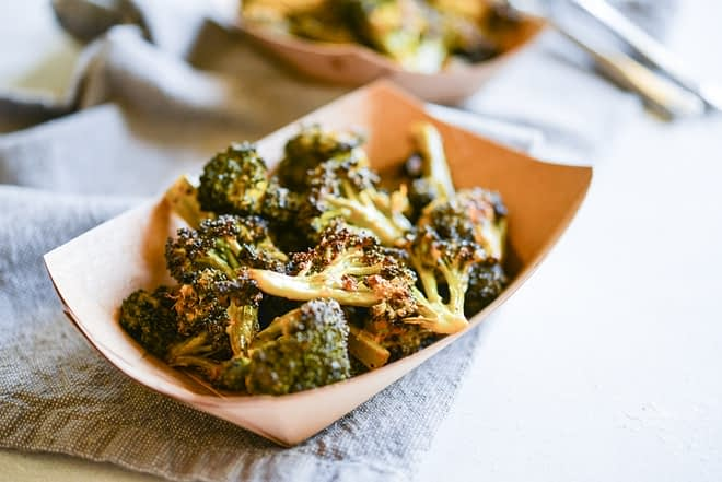 buffalo broccoli in a brown paper food boat on top of a grey napkin