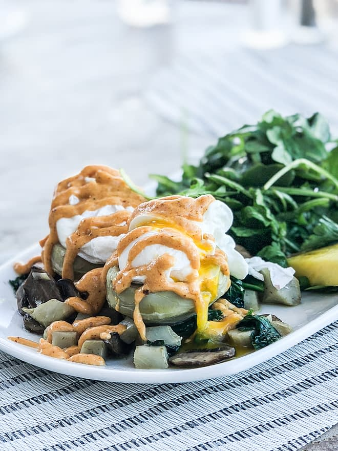 a breakfast hash plate with fried eggs and an orange sauce drizzled on top