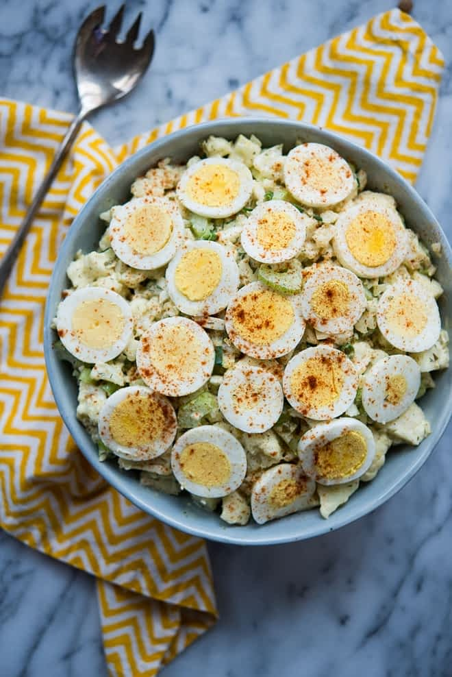 "overhead shot of bowl of Cauliflower ""Potato"" Salad with zig zag yellow napkin on a marble tabletop"