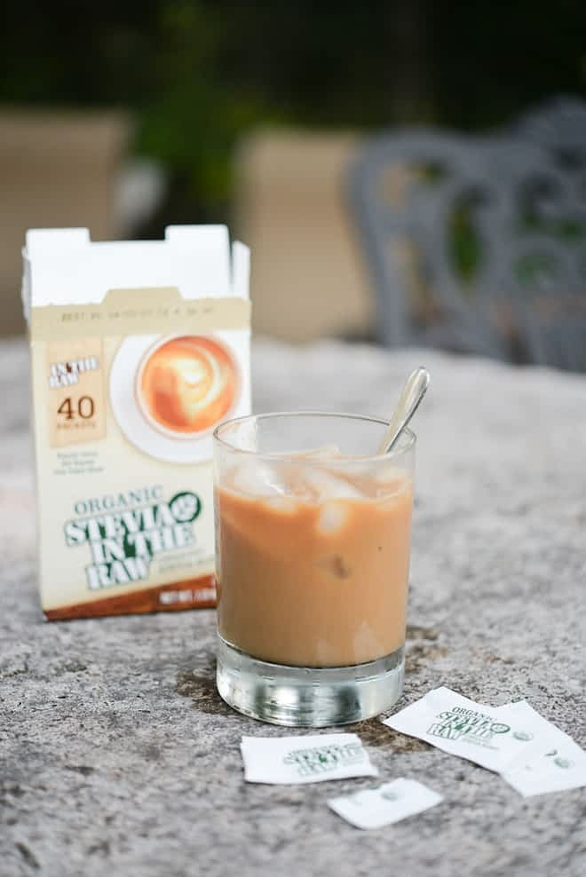 glass cup filled with caramel colored coffee with two packets of stevia in the raw on the table