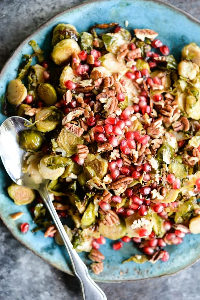This Pomegranate Brussels Sprouts Slaw is tangy with a hint of sweet, crunch from the pecans, and the perfect side dish for your holiday table!
