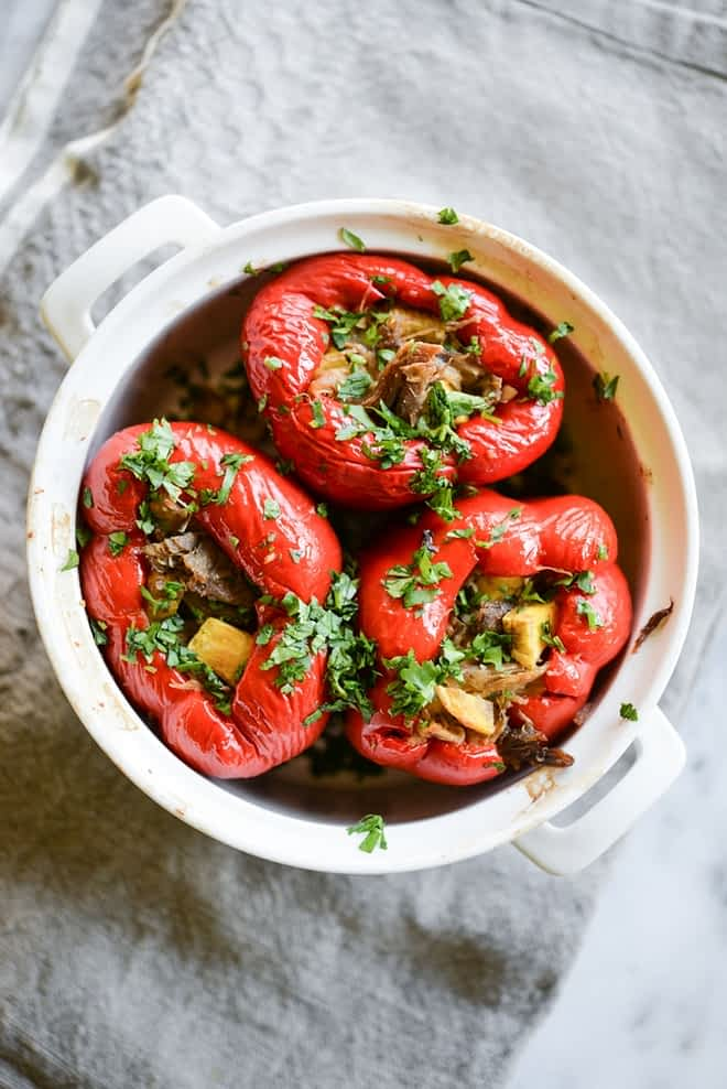 overhead view of meal prep carnitas stuffed red bell peppers in a white casserole dish